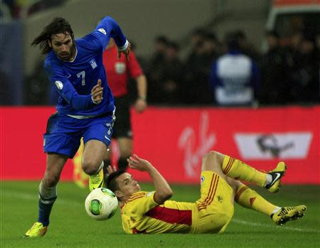 Samaras of Greece controls the ball past Hoban of Romania during their 2014 World Cup qualifying soccer match in Bucharest