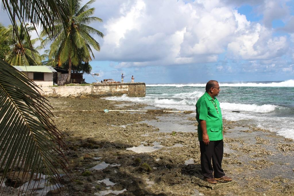"Marshall Islands President Christopher Loeak, pictured in 2014 in front of his home in Majuro, raised the height of a seawall around his property following tidal floods in response to a ""climate emergency"""
