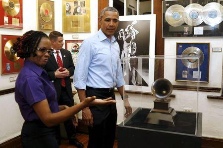U.S. President Barack Obama looks at a Grammy Award as he gets a tour of the Bob Marley Museum from staff member Natasha Clark (L) in Kingston, Jamaica April 8, 2015. REUTERS/Jonathan Ernst