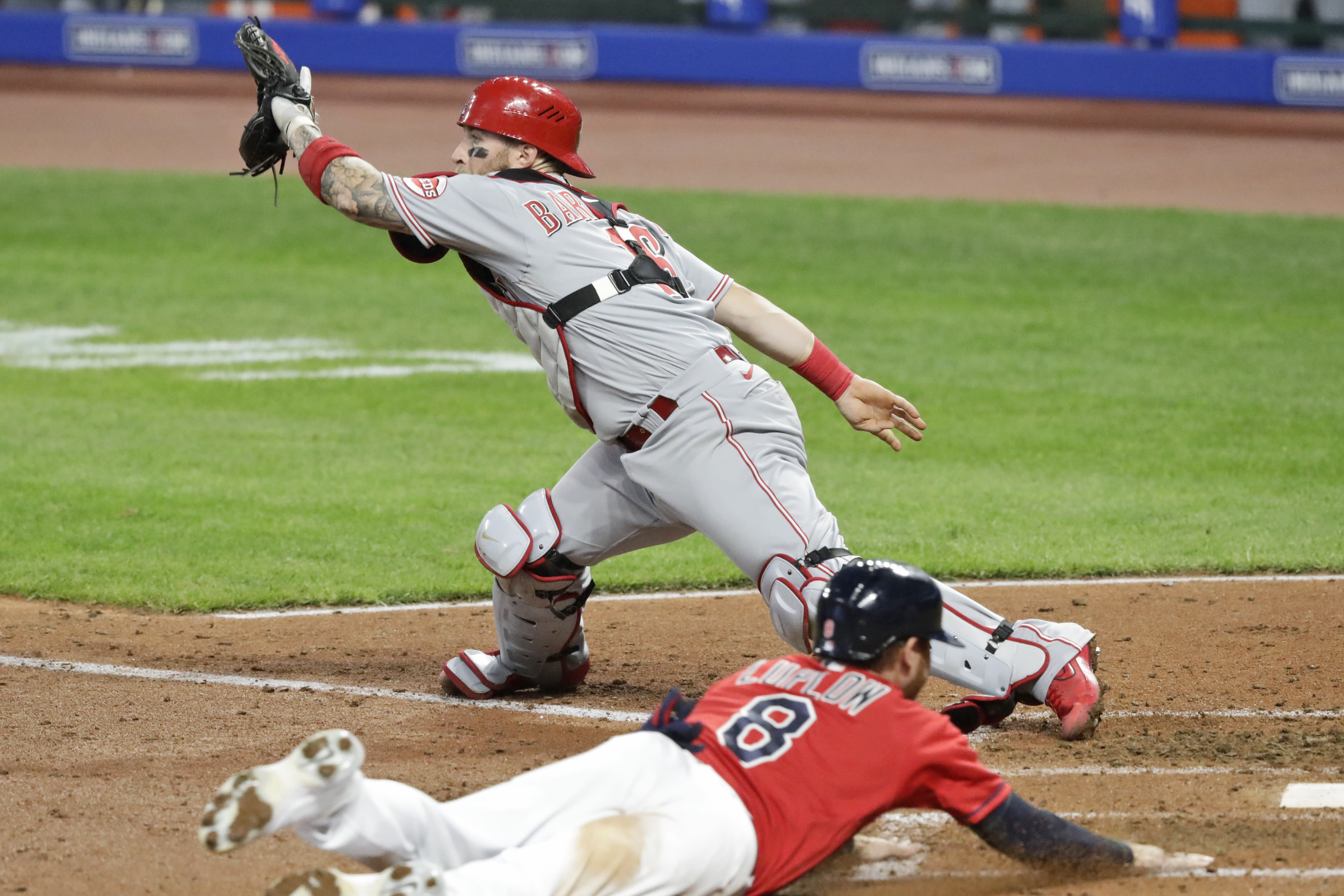 Cleveland Indians' Jordan Luplow, bottom, scores as Cincinnati Reds catcher Tucker Barnhart waits for the ball in the fifth inning in a baseball game, Wednesday, Aug. 5, 2020, in Cleveland. (AP Photo/Tony Dejak)