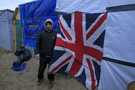 "Terer, a migrant from Syria, shows a Union Jack sleeping bag used as a door to his shelter in a camp for migrants called the ""jungle"", near Calais, northern France, February 21, 2016. REUTERS/Pascal Rossignol"