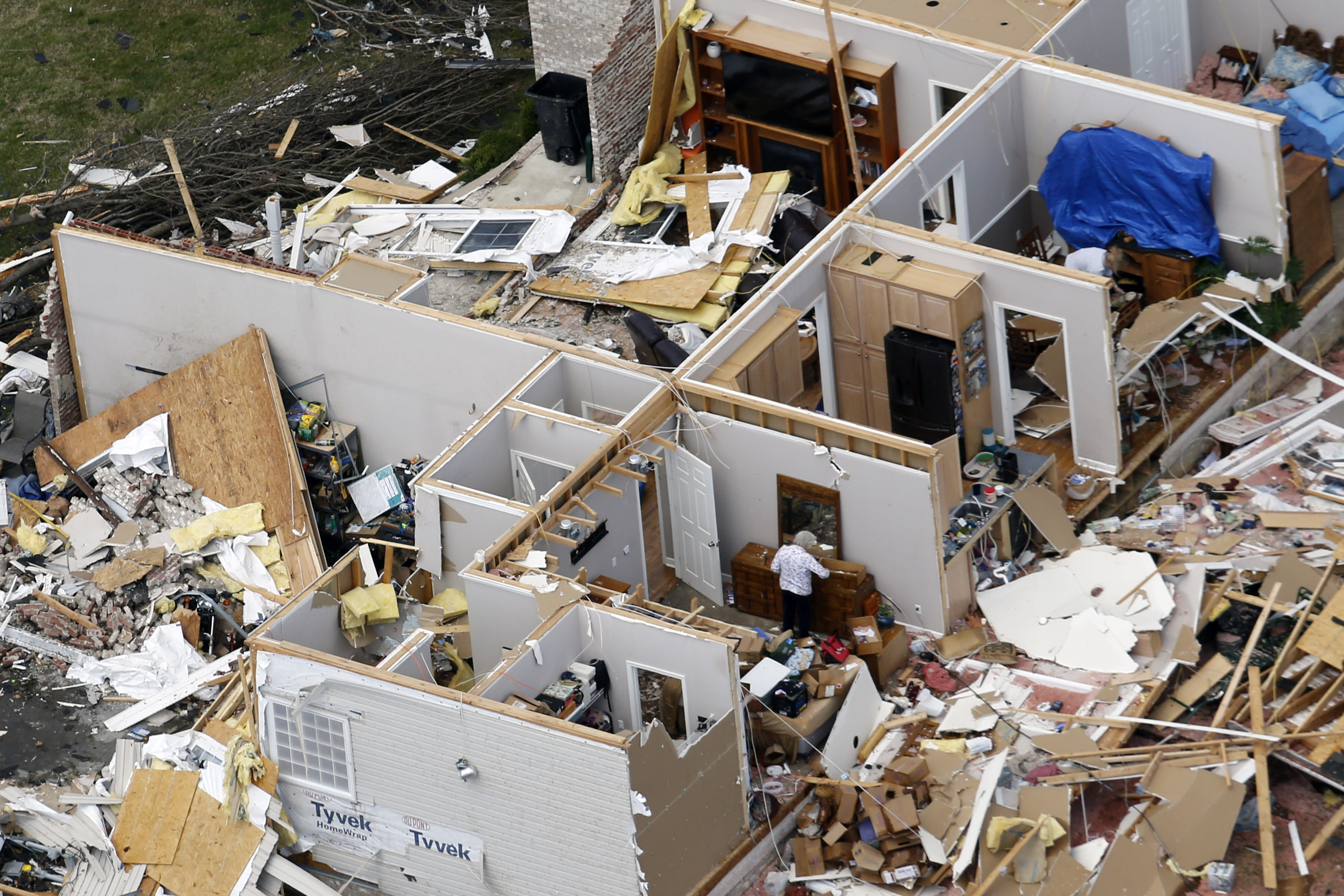 A woman salvages item from a destroyed home Tuesday, March 3, 2020, near Lebanon, Tenn. Tornadoes ripped across Tennessee early Tuesday, shredding more than 140 buildings and burying people in piles of rubble and wrecked basements. (AP Photo/Mark Humphrey)