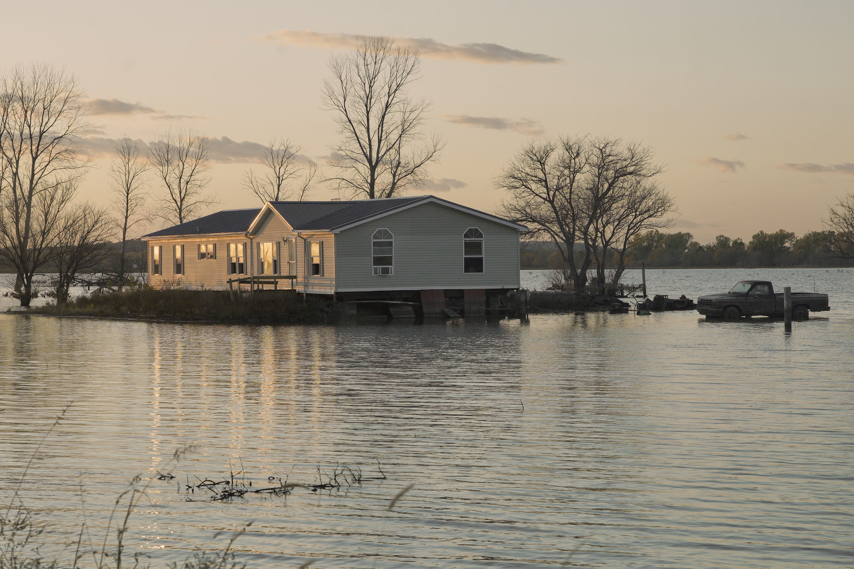 In this Tuesday, Oct. 22, 2019 photo, a home is surrounded by floodwaters in Bartlett, Iowa. Flooding along the Missouri River has stretched on for seven months in places and could endure through the winter, leaving some Upper Midwest farmland and possibly some homes encased in ice. (AP Photo/Nati Harnik)