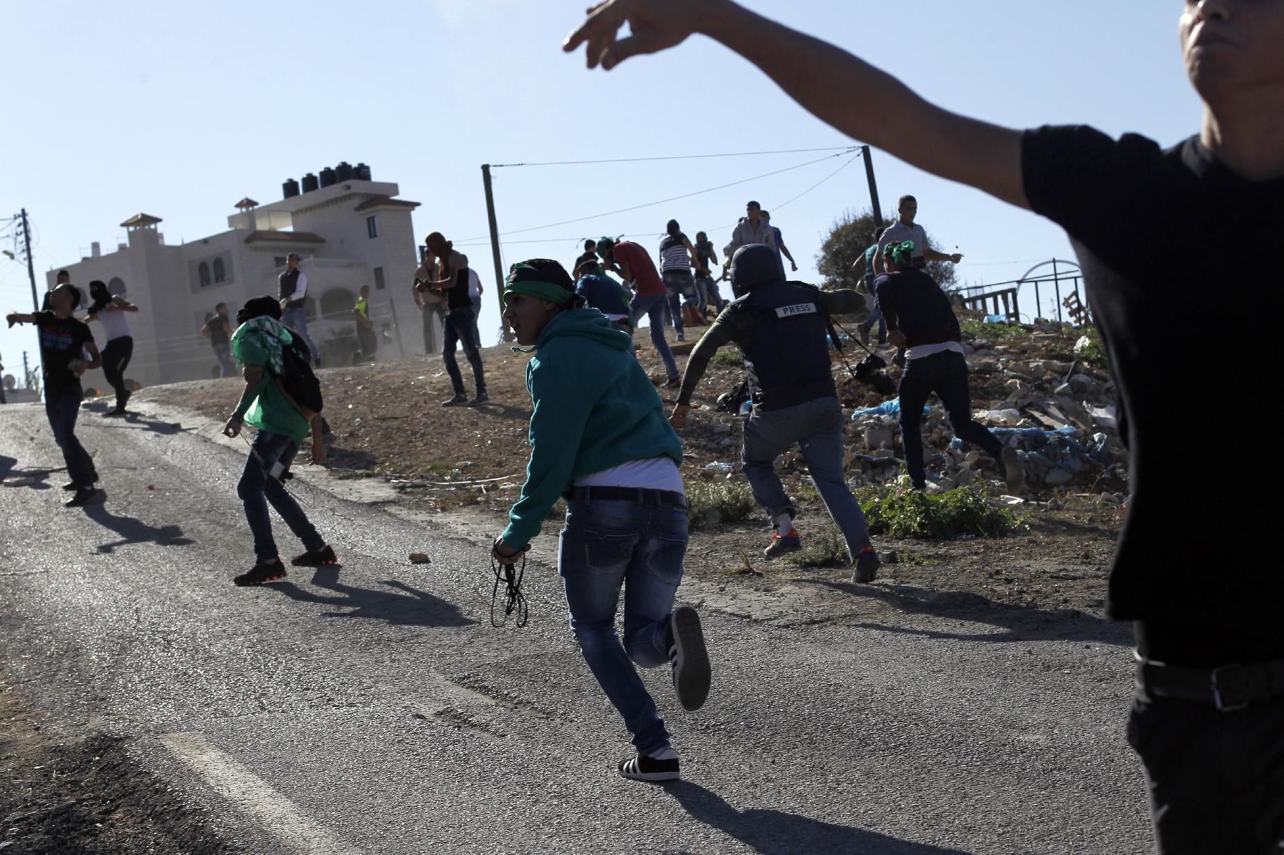 Palestinians from the Jalazoun refugee camp clash with Israeli security forces at the entrance of the Jewish West Bank settlement Beit El, north of Ramallah, after a march against Israeli restrictions on the Al-Aqsa mosque, October 24, 2014 (AFP Photo/Abbas Momani)