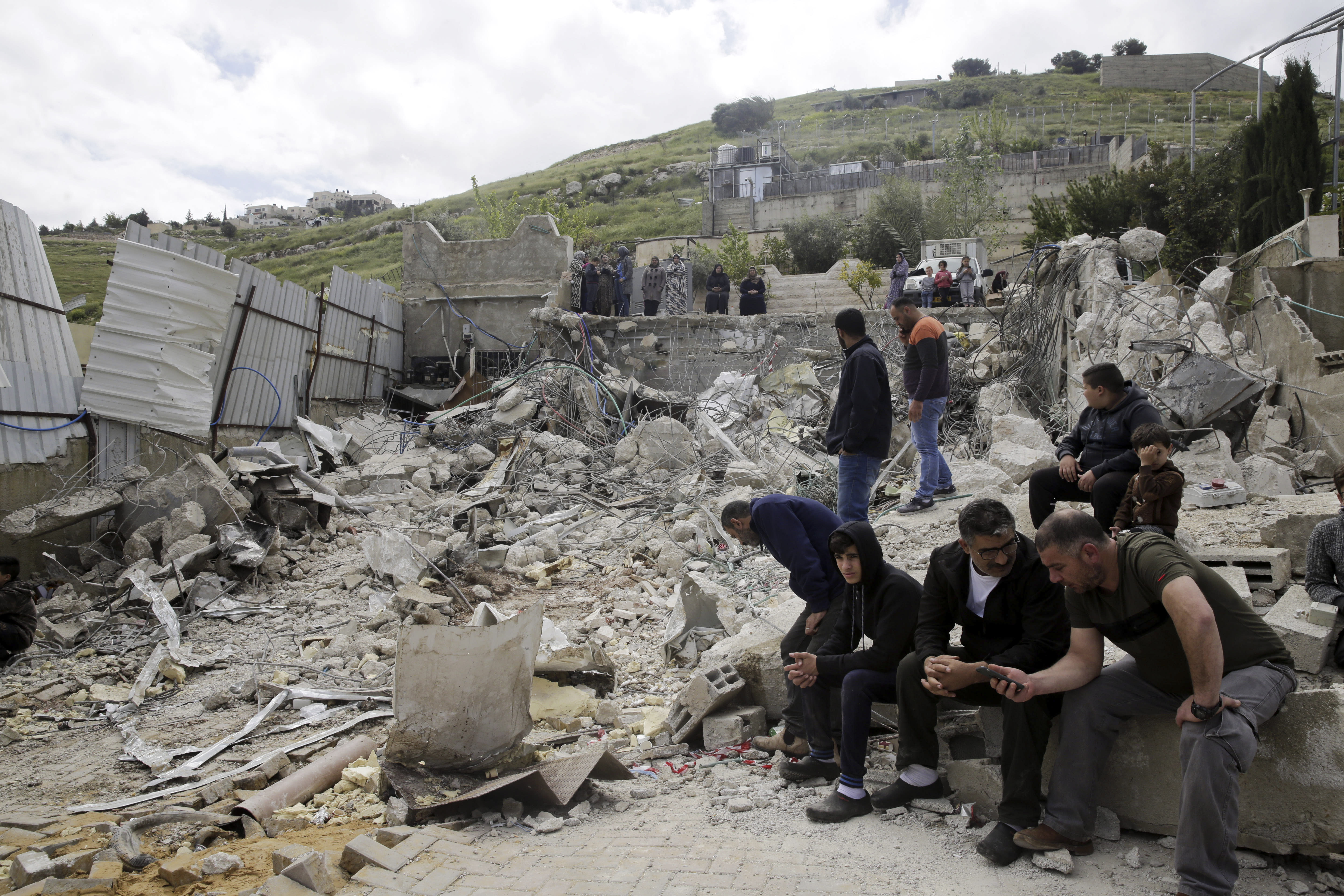 """File - In this April 17, 2019 file photo, Palestinians sit by a family house destroyed by Israeli authorities in east Jerusalem's neighborhood of Silwan. Scores of Palestinian-owned residences in east Jerusalem now face demolition by Israeli authorities after the Supreme Court dismissed residents' appeal on the grounds that the houses were built illegally in a city park. Activists and Palestinian residents of the so-called """"Peace Forest"""" say the case highlights the city's discriminatory housing policies, as construction by a nationalist Jewish organization accelerates in the same park. (AP Photo/Mahmoud Illean, File)"""