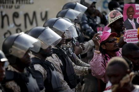 National Police officers stand guard next to the Provisional Electoral Council building as supporters of PHTK political party attend a speech during a demonstration demanding the organization of a postponed presidential runoff election in Port-au-Prince, Haiti, April 24, 2016. REUTERS/Andres Martinez Casares