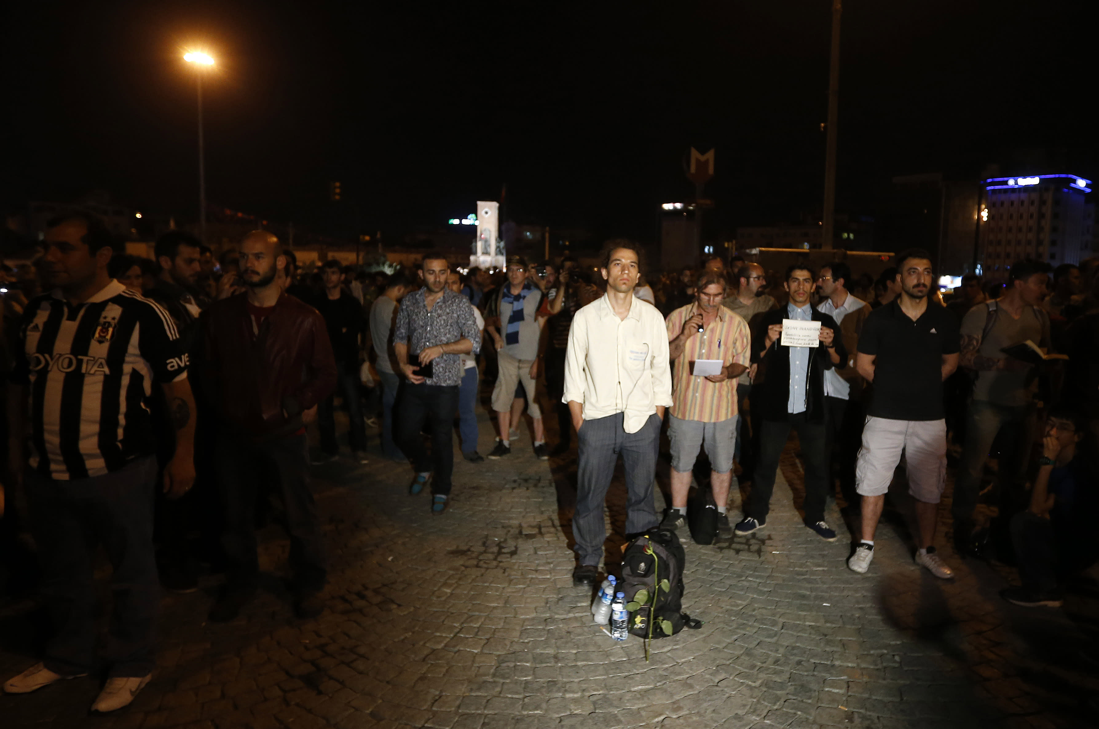 Erdem Gunduz, centre, stands silently on Taksim Square in Istanbul, Turkey, early Tuesday, June 18, 2013. After weeks of confrontation with police, sometimes violent, Turkish protesters are using a new form of resistance: standing silently. The development started late Monday when a solitary man began standing in passive defiance against Prime Minister Recep Tayyip Erdogan's authority at Istanbul's central Taksim Square. The square has been sealed off from mass protests since police cleared it over the weekend. The man has identified himself as Erdem Gunduz, a performance artist. His act has sparked imitation by others in Istanbul and other cities. It has provoked widespread comment on social media. (AP Photo/Petr David Josek)