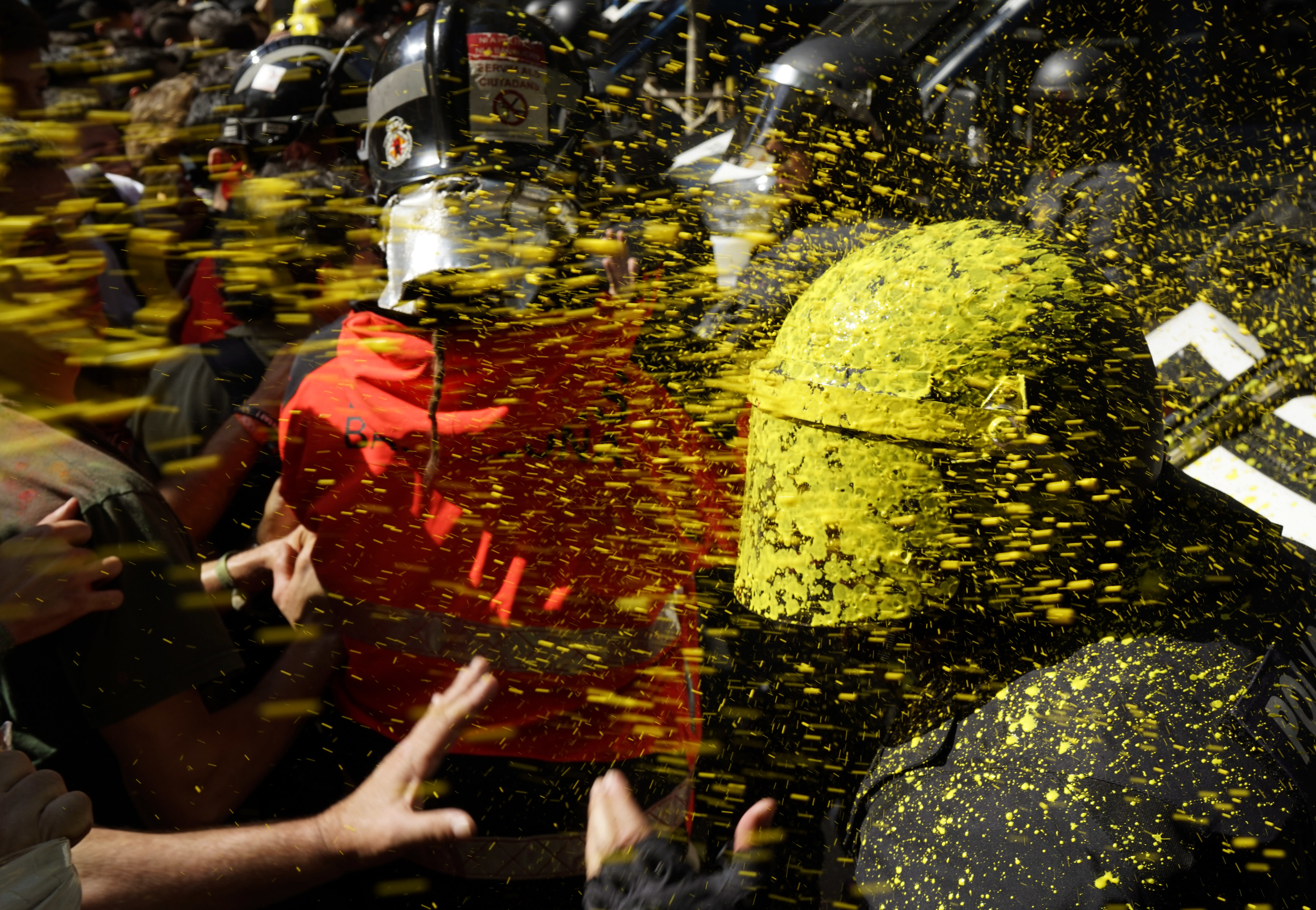 Pro independence demonstrators throw paint at Catalan police officers during clashes in Barcelona, Spain, on Saturday, Sept. 29, 2018. Catalan separatists clashed with police on Saturday in downtown Barcelona as tensions increase before the anniversary of the Spanish region's illegal referendum on secession that ended in violent raids by security forces. (AP Photo/Daniel Cole)