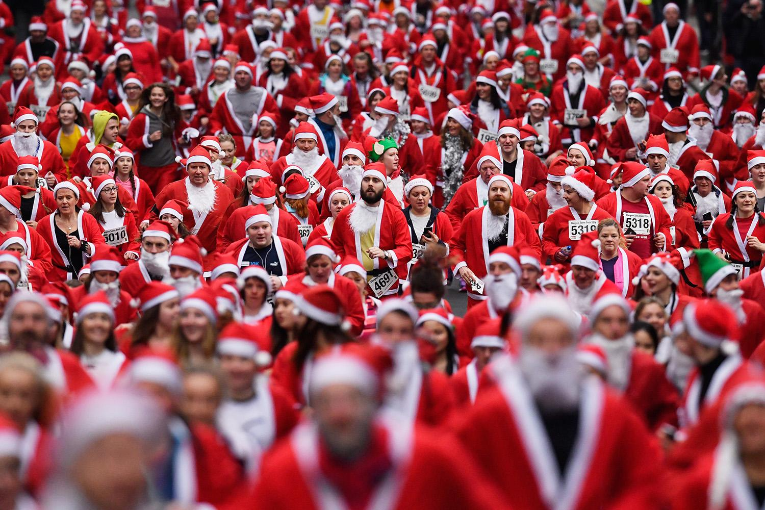 """<p>Thousands of people dressed as Santa participate in """"The Santa Dash"""" in Glasgow, Scotland. (Photo: Jeff J Mitchell/Getty Images) </p>"""