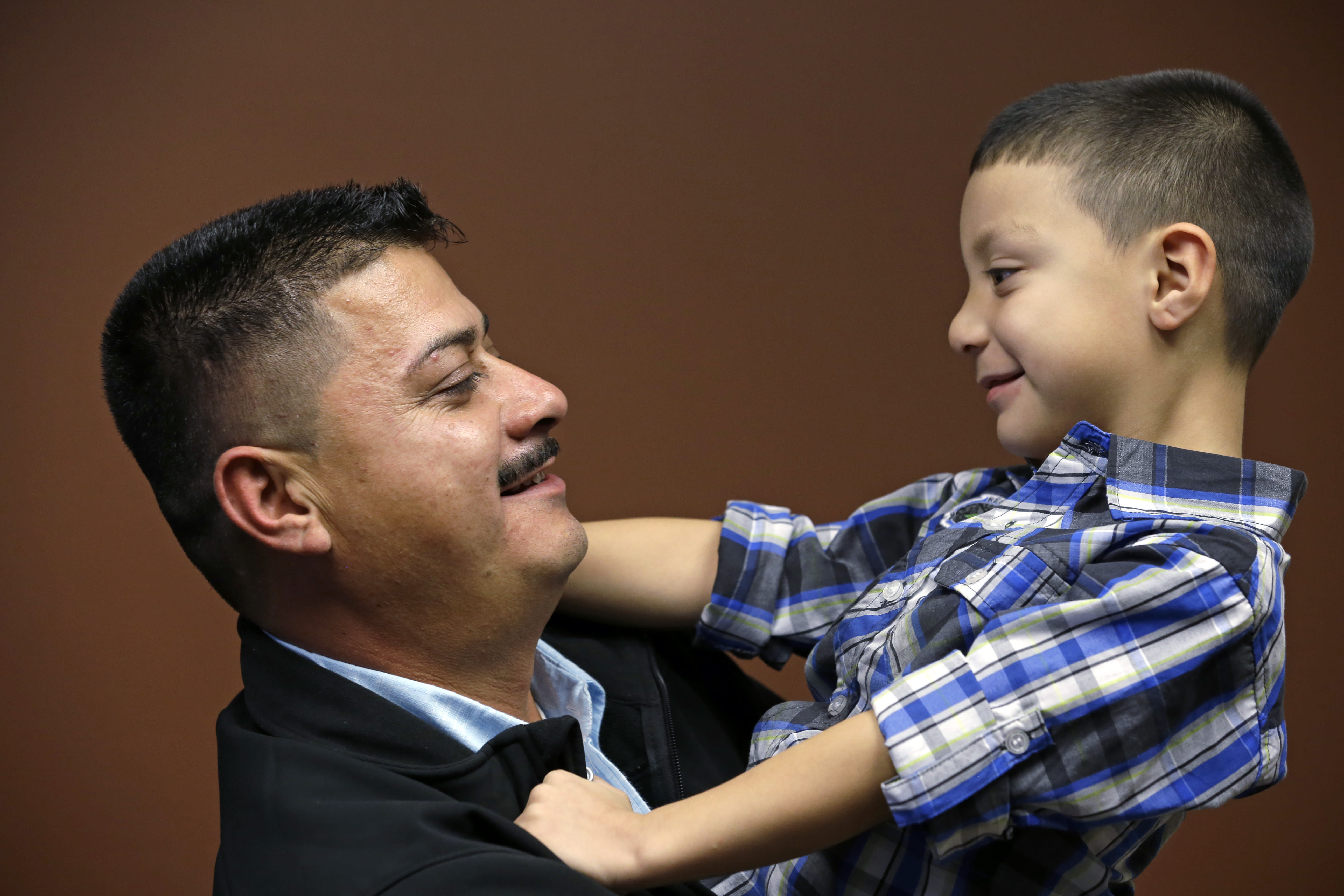 FILE - In this Oct. 17, 2014, file photo, Ignacio Lanuza holds his son, Isaiah, 4, as he has his photo taken in Seattle. A federal judge on Tuesday, Oct. 29, 2019, criticized the Justice Department for seeking legal fees from Lanuza, a Mexican immigrant who was the victim of a forgery by a government lawyer. (AP Photo/Elaine Thompson, File)