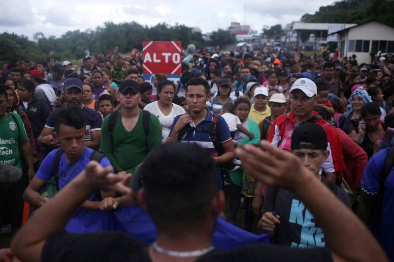 Migrants from Central American, part of a caravan travelling to the U.S., wait to cross into Mexico at the border between Guatemala and Mexico, in El Ceibo