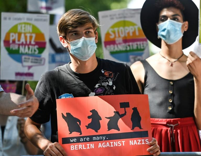 """As politicians slammed the rally, a small number of counter-protesters gathered, one holding a sign reading """"we are many. Berlin against Nazis"""" (AFP Photo/John MACDOUGALL)"""