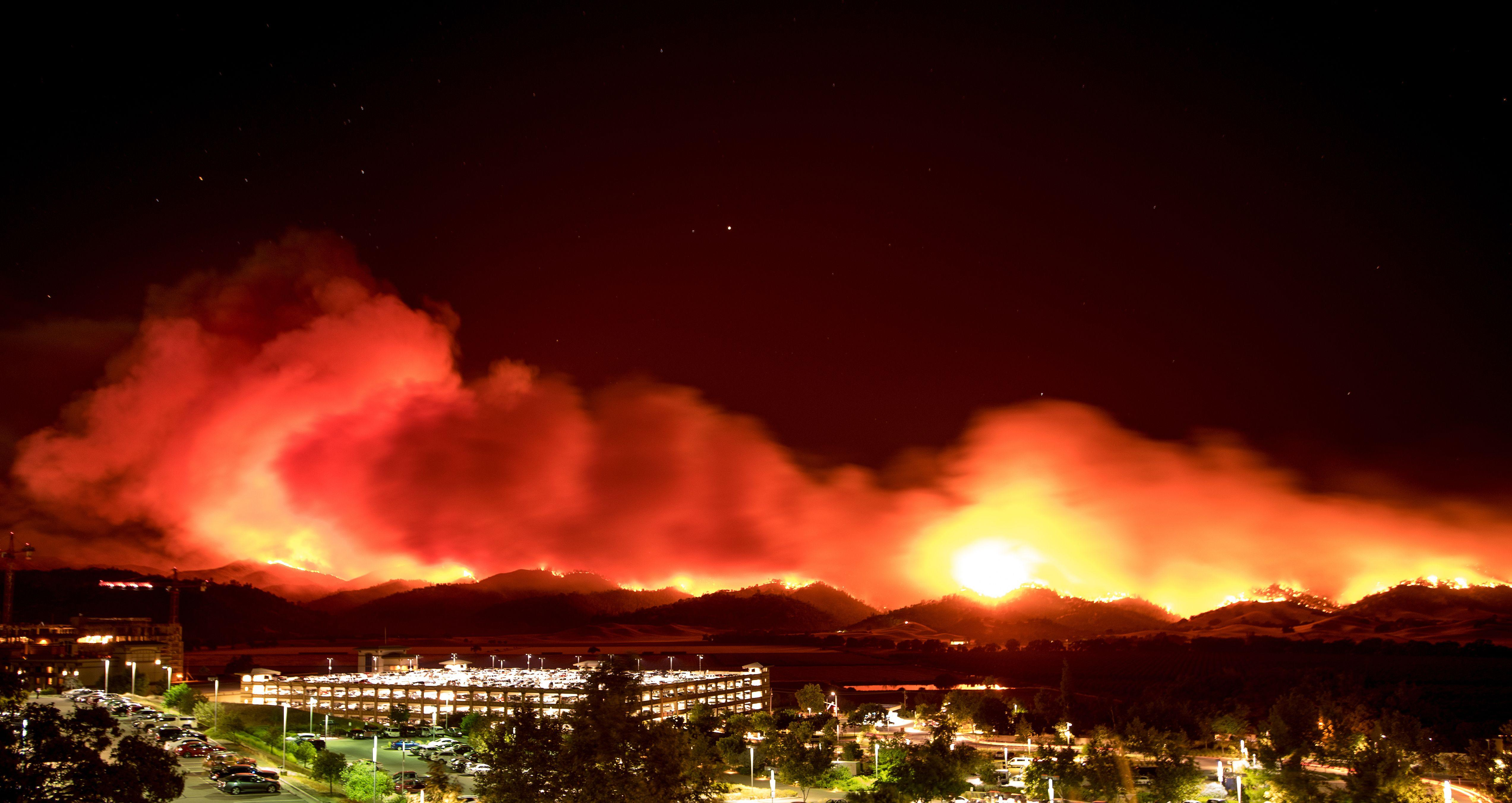 <p>In this long exposure photo, fire burns behind Cache Creek Casino Resort near Guinda, Calif. near on July 1, 2018. (Photo: Josh Edelson/AFP/Getty Images) </p>