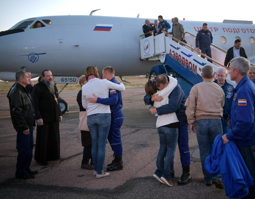 Aleksey Ovchinin, centre, and Nick Hague, right, embrace their families after landing (AFP Photo/Bill INGALLS)