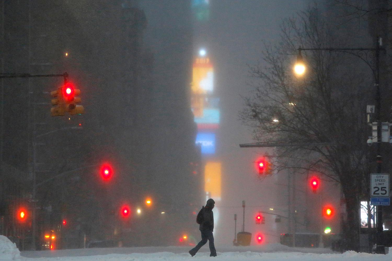 <p>Times Square is seen in the background as a man walks along West 59th street during a snow storm in New York, March 14, 2017. (Andrew Kelly/Reuters) </p>