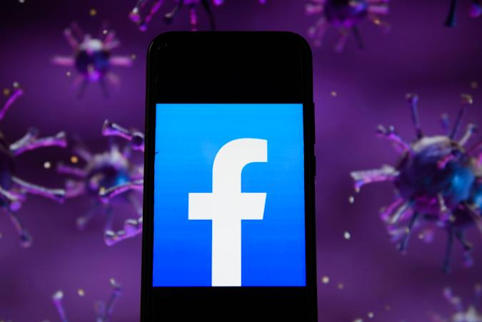POLAND - 2020/04/28: In this photo illustration a facebook logo displayed on a smartphone with a COVID 19 sample image in the background. (Photo Illustration by Omar Marques/SOPA Images/LightRocket via Getty Images)