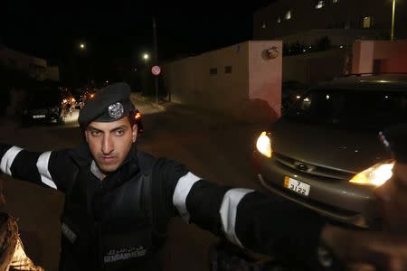 Jordanian policemen try to keep journalists out as a convoy carrying Japanese envoy State Minister for Foreign Affairs Yasuhide Nakayama leaves the Japanese Embassy after the news of the killing of Japanese hostage Kenji Goto in Amman January 31, 2015. REUTERS/Muhammad Hamed