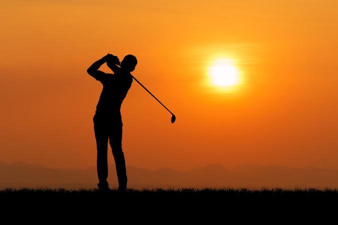Silhouette of golfer against sunset
