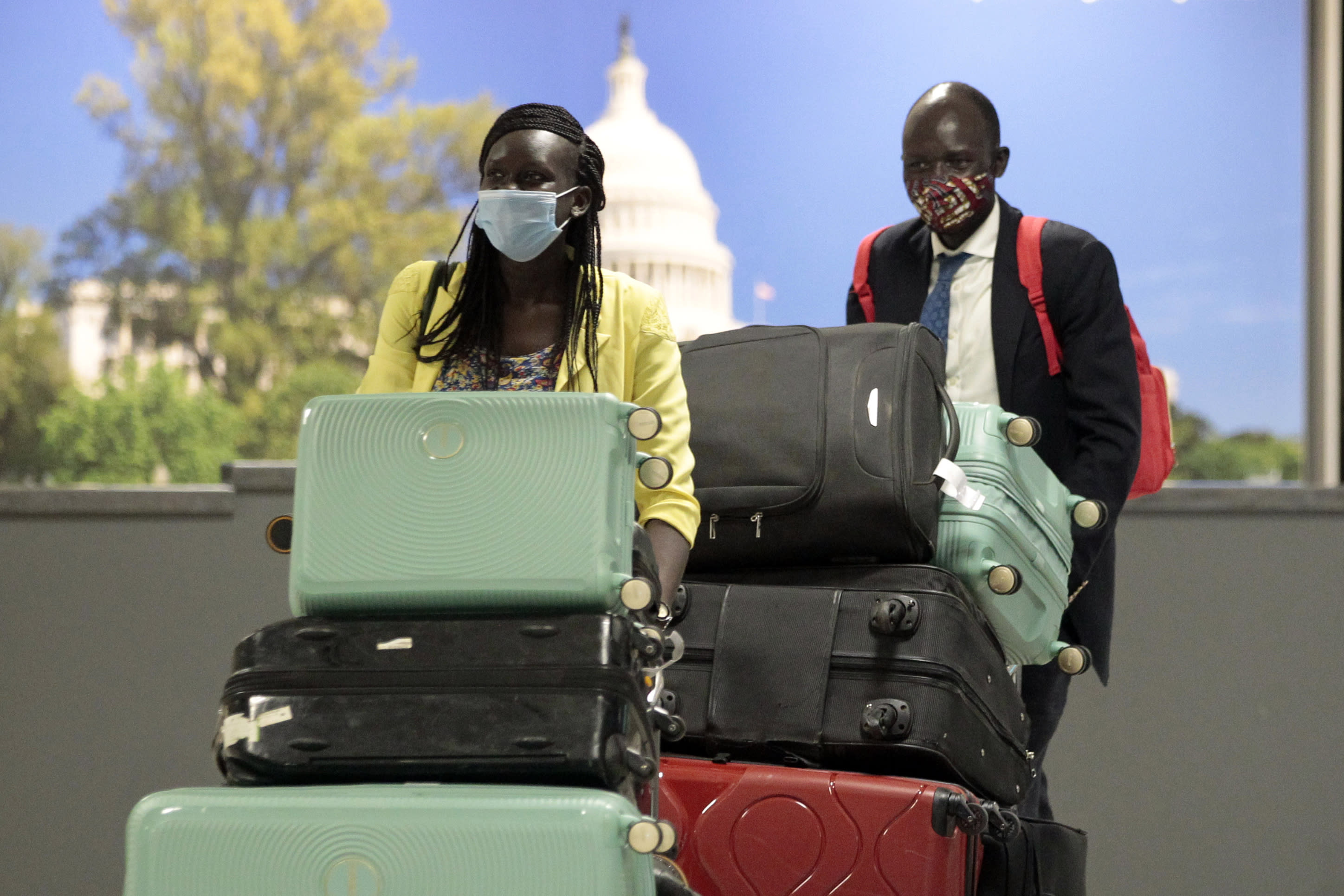Peter Biar Ajak, background, arrives with his wife Nyathon Hoth Mai, front, and kids at Washington Dulles International Airport in Chantilly, Va.,Thursday, July 23, 2020. (AP Photo/Luis M. Alvarez)