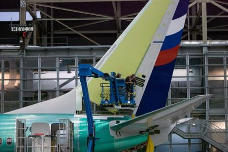 FILE PHOTO: Boeing employees work on the tail of a Boeing 737 NG at the Boeing plant in Renton, Washington