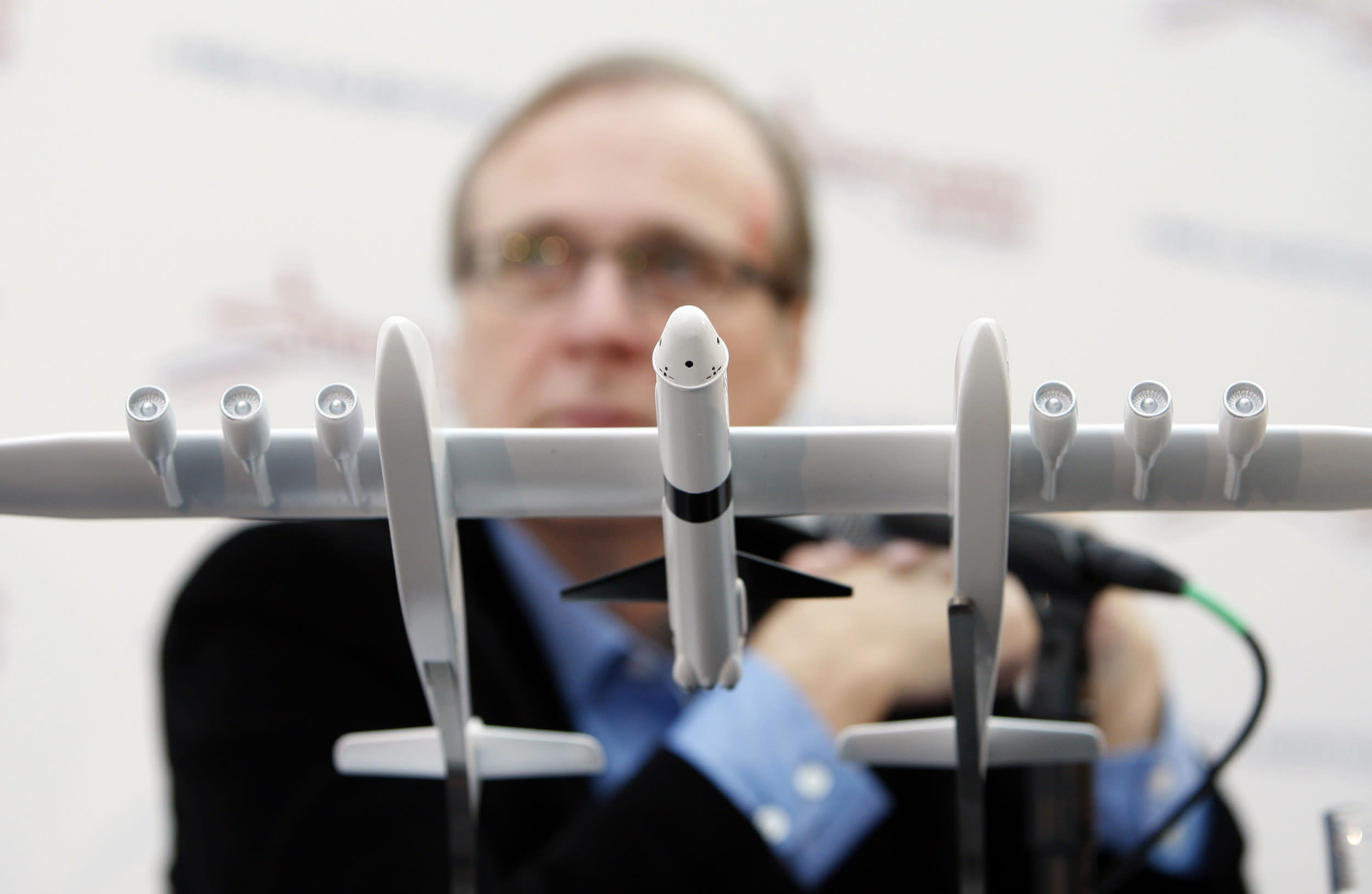 Paul Allen, co-founder of Microsoft Corp., sits behind a model aircraft during a news conference for the launch of his new venture Stratolaunch Systems Inc. in Seattle, Washington, U.S., on Tuesday, Dec. 13, 2011. Allen said Stratolaunch Systems Inc. will bring 'airport-like operations' to space flights, including eventual human missions. The first flight is planned within five years. Photographer: Kevin P. Casey/Bloomberg via Getty Images