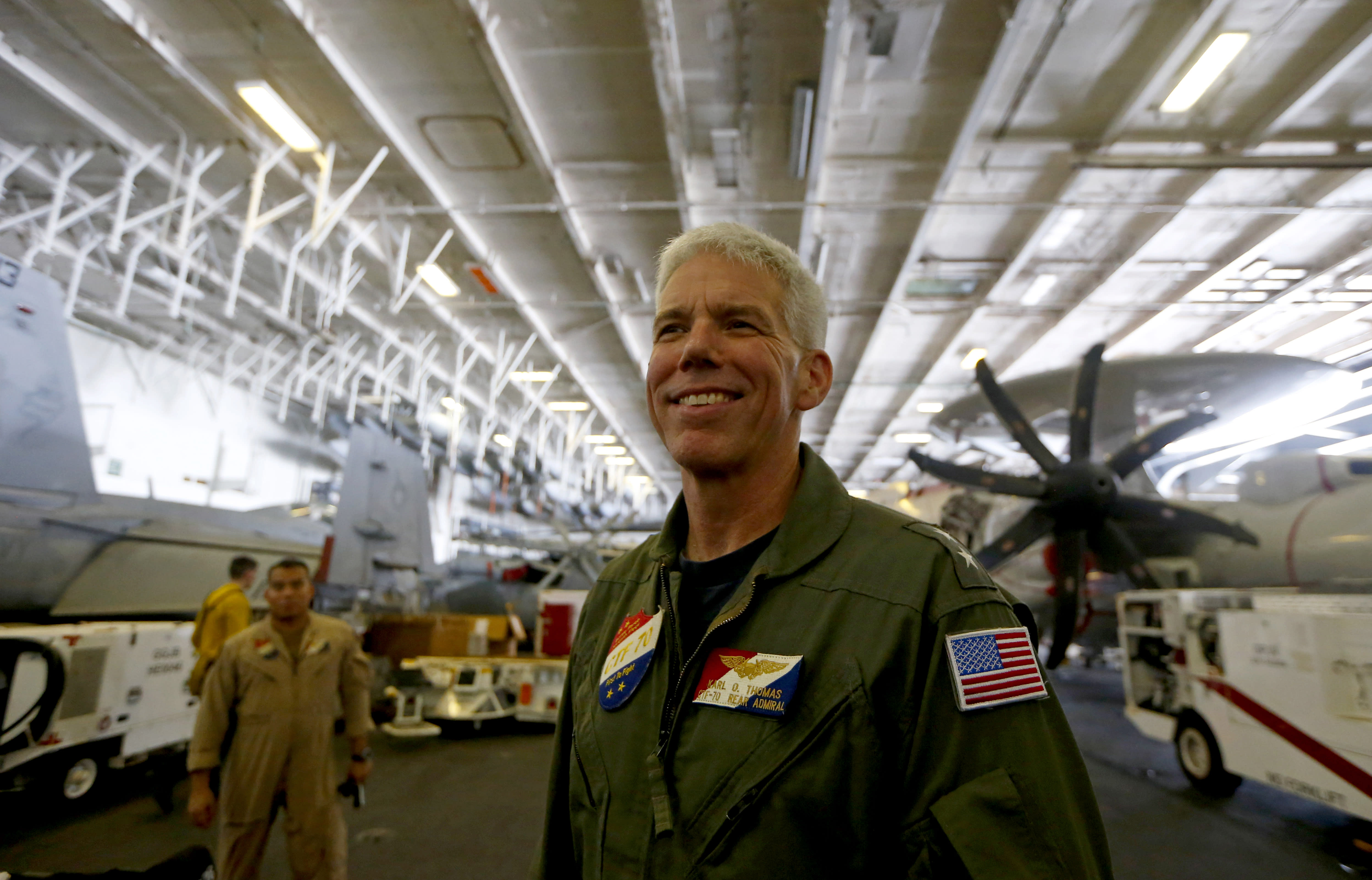 Rear Admiral Karl Thomas, Task Force 70/Commander, Carrier Strike Group 5, poses before an E-2 Hawkeye plane following a media interview aboard the U.S. aircraft carrier USS Ronald Reagan off South China Sea Tuesday, Aug. 6, 2019, west of the Philippines. The USS Ronald Reagan is cruising in international waters in the South China Sea amid tensions in the disputed islands, shoals and reefs between China and other claimant-countries as Philippines, Vietnam and Malaysia. (AP Photo/Bullit Marquez)