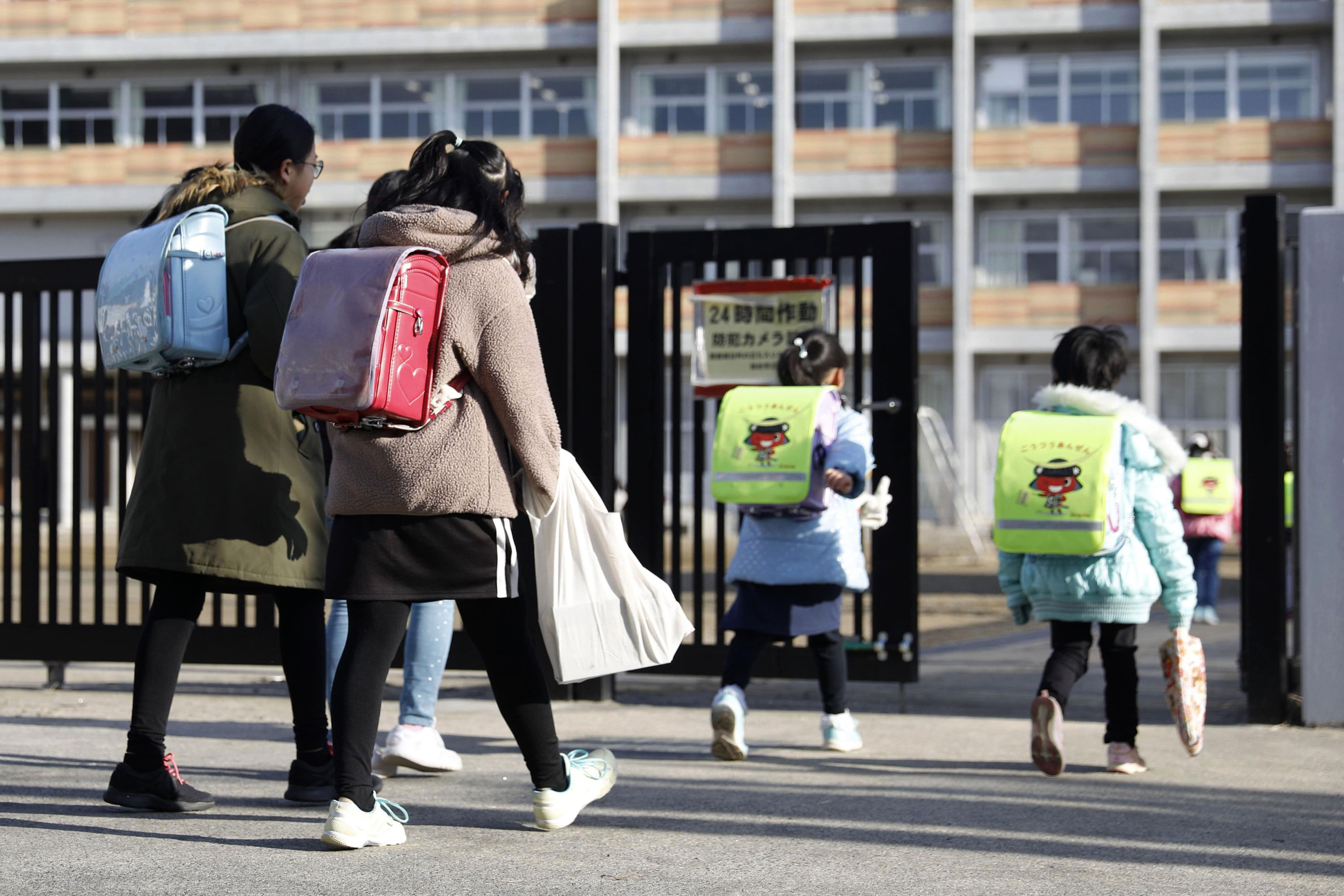 Students arrives at their elementary school in Sendai, northern Japan, Friday morning, Feb. 28, 2020, a day after Japanese Prime Minister Shinzo Abe's announcement. Abe asked all elementary, middle and high schools nationwide on Thursday to close until late March from March 2 to help control the spread of the new virus in the country. (Hironori Asakawa/Kyodo News via AP)