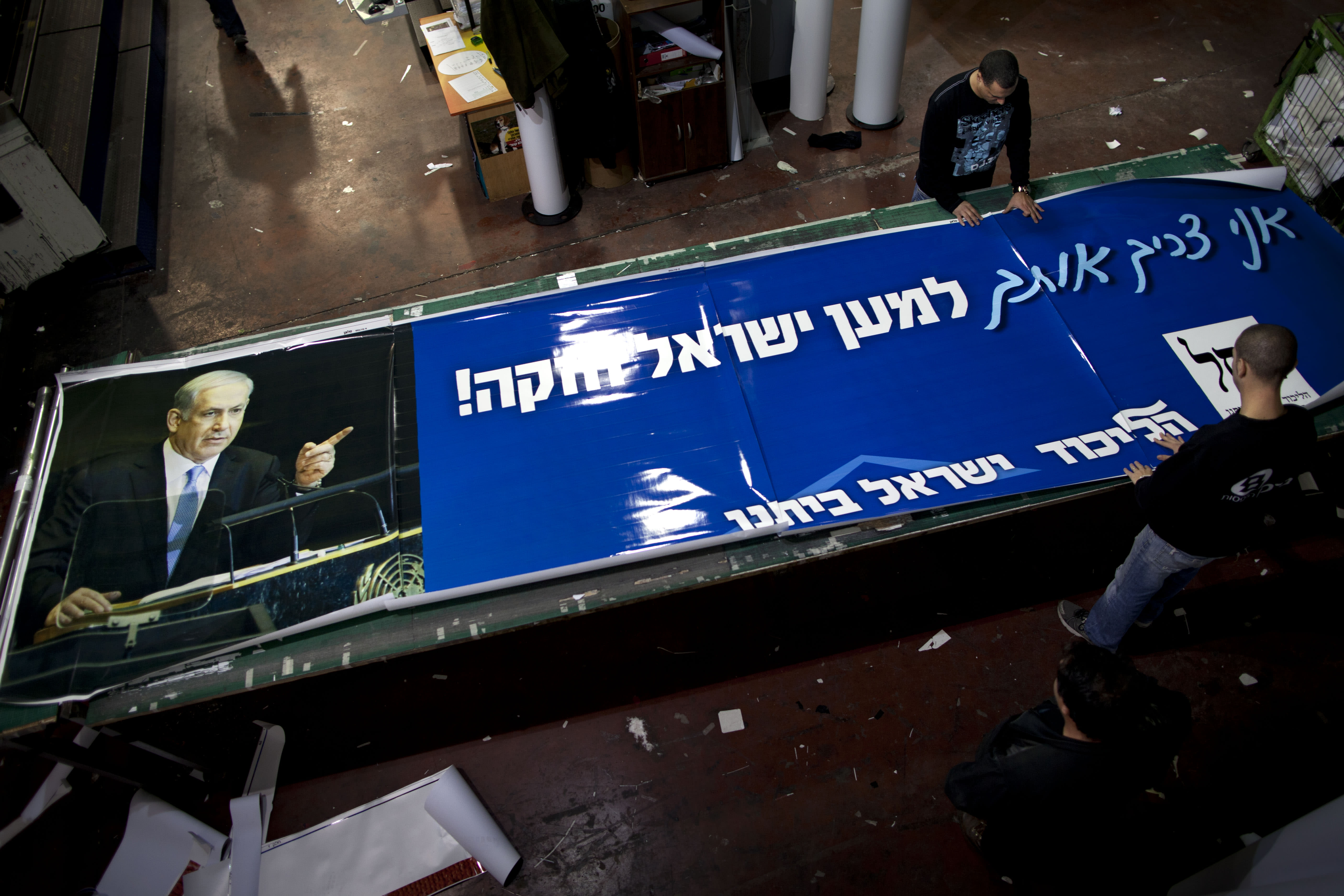 """In this photograph made on Sunday, Jan. 13, 2013, a print house employes work on an election campaign billboard of Israeli Prime Minister and Likud Party leader Benjamin Netanyahu, in the central Israeli Town of Petah Tikva. Palestinian officials largely view Benjamin Netanyahu's expected re-election with despair, fearing the Israeli hardliner's ambitious plans for settlement construction over the next four years could prove lethal to their dreams of a state. Hebrew on billboards reads - """" I need you for strong Israel"""". (AP Photo/Oded Balilty)"""