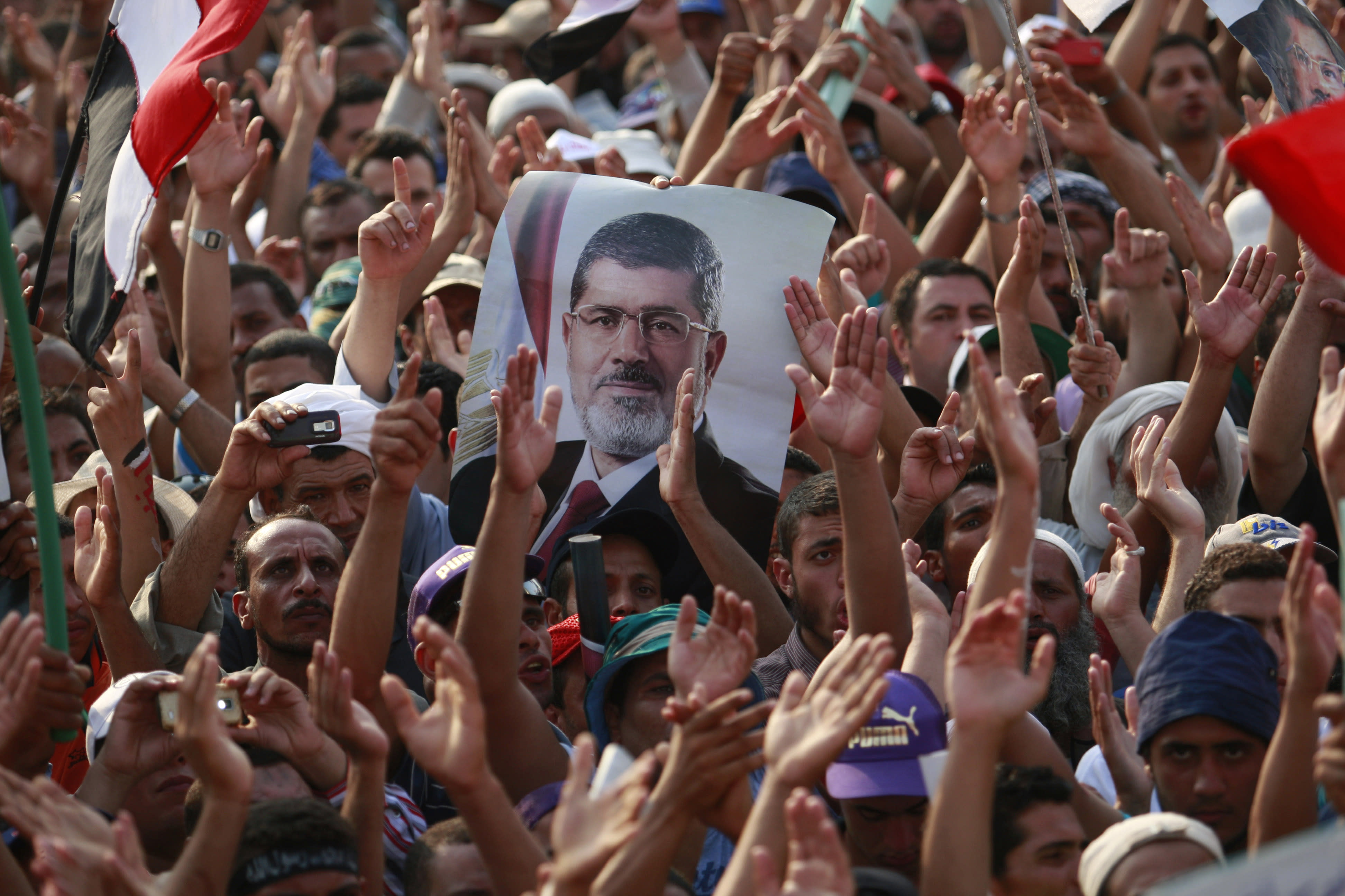 """Supporters of ousted President Mohammed Morsi, seen in poster, protest in Nasr City, Cairo, Egypt, Tuesday, July 9, 2013. After days of deadlock, Egypt's military-backed interim president named a veteran economist as prime minister on Tuesday and appointed pro-democracy leader Mohamed ElBaradei as a vice president, while the army showed its strong hand in shepherding the process, warning political factions against """"maneuvering"""" that impedes the transition. (AP Photo/Nasser Shiyoukhi)"""