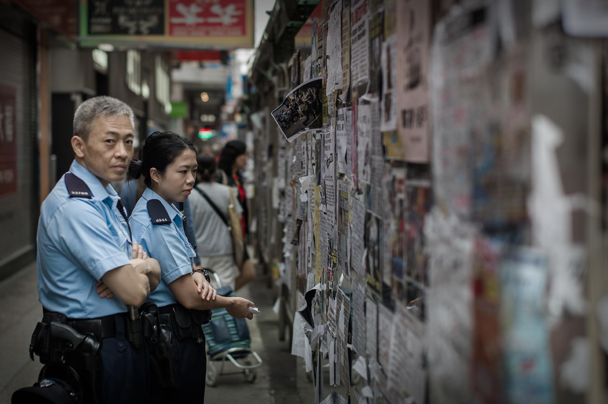 Members of the police look at pro-democracy posters displayed on a bus stop near the encampment of a protest site in the Mongkok district of Hong Kong on November 12, 2014 (AFP Photo/Philippe Lopez)