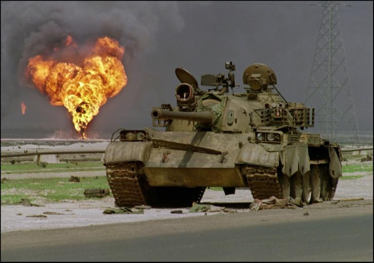 An abandoned Iraqi Soviet-made T-62 tank sits in the Kuwaiti desert as an oil well burns in the background, on April 2, 1991 (AFP Photo/Pascal GUYOT)