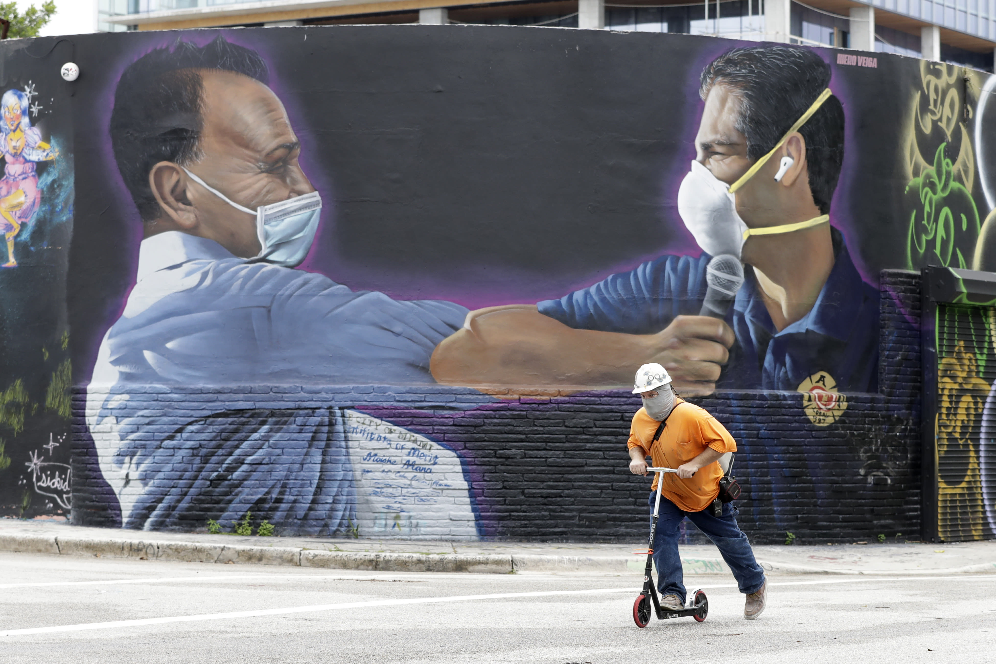 """A construction worker rides a scooter past a mural by Hiero Veiga of billionaire businessman Moishe Mana, left, and City of Miami Mayor Francis X. Suarez wearing masks Monday, July 13, 2020, in the Wynwood Arts District of Miami. Florida's rapidly increasing number of coronavirus cases is turning Miami into the """"epicenter of the pandemic,"""" a top doctor warned Monday, while an epidemiologist called the region's situation """"extremely grave."""" (AP Photo/Wilfredo Lee)"""
