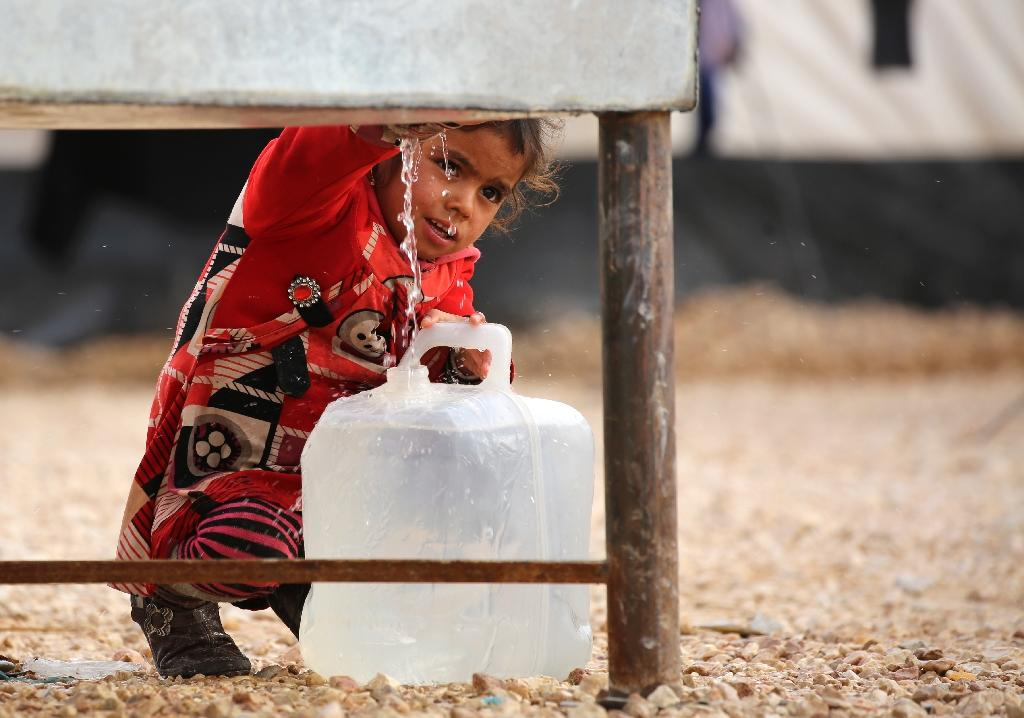 An Iraqi girl, who fled the Iraqi city of Mosul due to the fighting between government forces' and Islamic State group's jihadists, fills a container with water at the UN-run al-Hol refugee camp in Syria on December 5, 2016