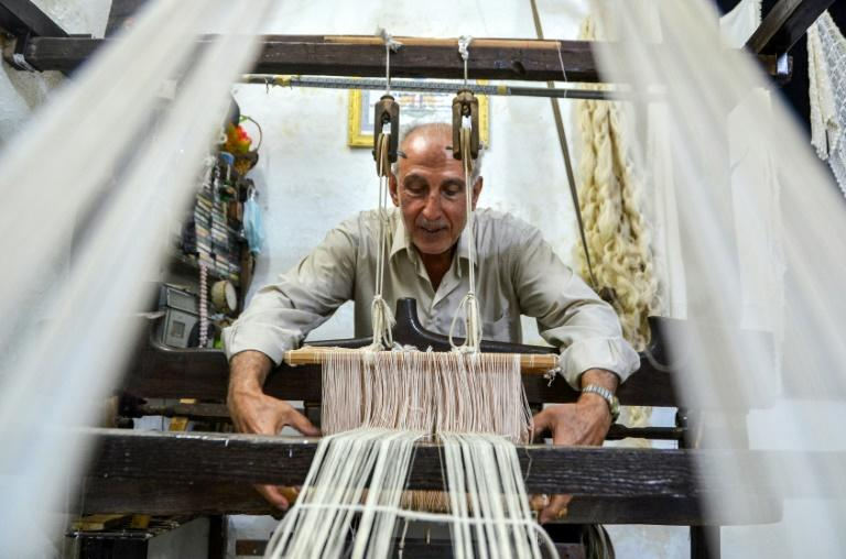 Muhammad Saud, a 65-year-old Syrian silk farmer, handweaves silk threads on a loom at his home workshop in the village of Deir Mama, in central-western Syria (AFP Photo/MAHER AL MOUNES)