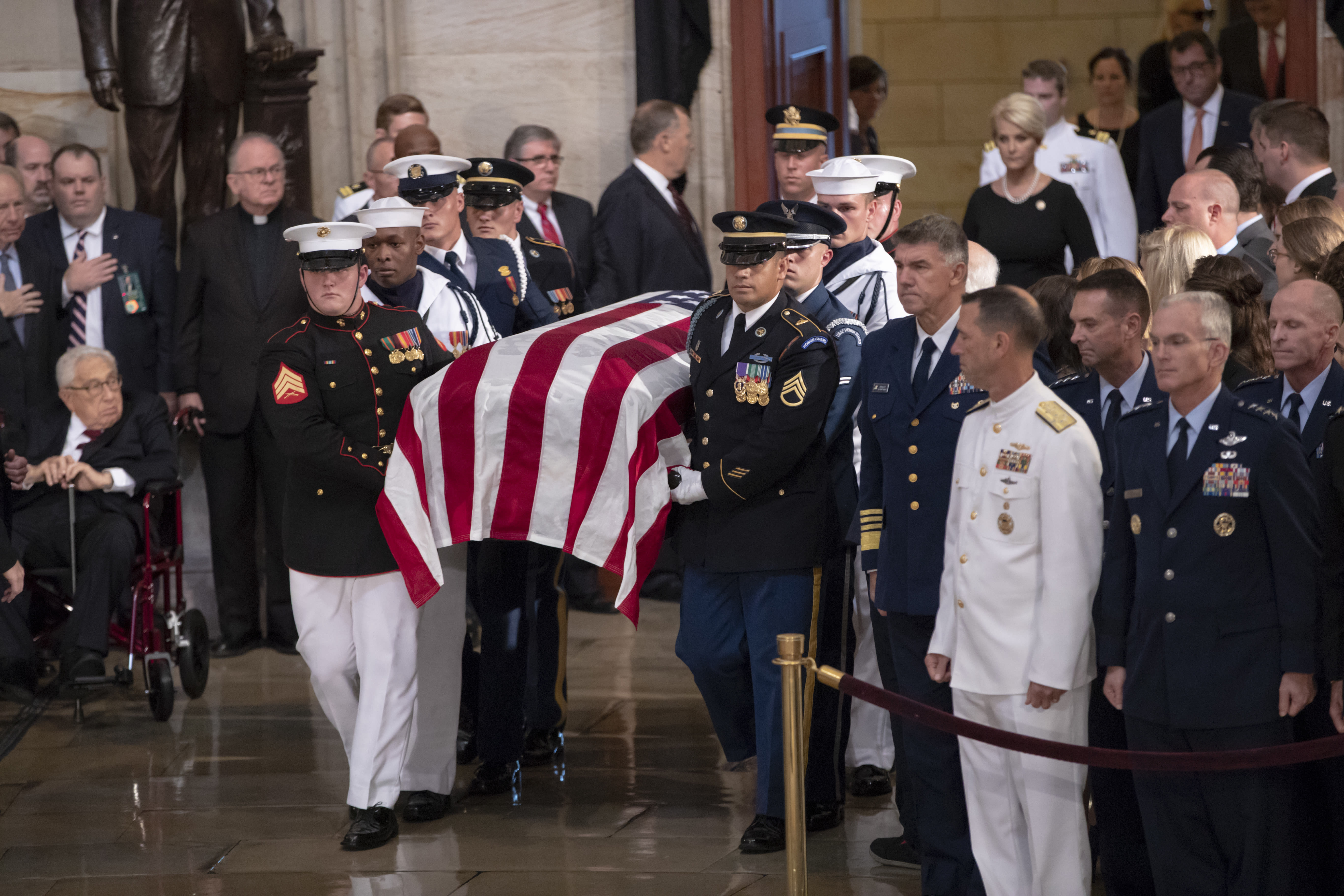 The flag-draped casket bearing the remains of Sen. John McCain of Arizona, who lived and worked in Congress over four decades, is carried into the U.S. Capitol rotunda, followed by his widow, Cindy McCain, upper right, for a farewell ceremony and public visitation, Friday, Aug. 31, 2018, in Washington. (AP Photo/J. Scott Applewhite)