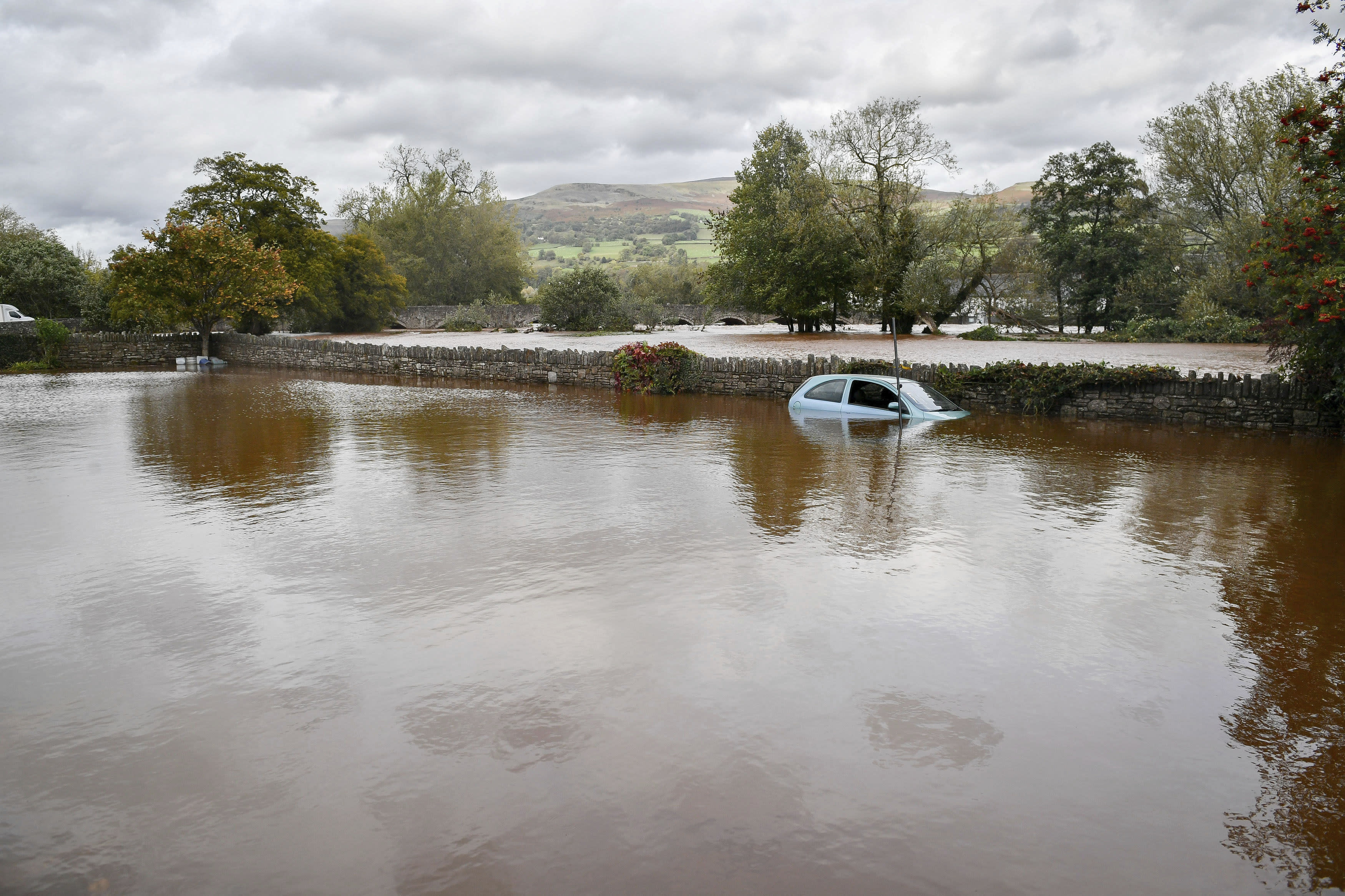 A stranded vehicle parked in flood water in a car park next to the A4077 where an amber weather warning is in force across the region as heavy rain is causing flooding, in Crickhowell, Wales, Saturday, Oct. 13, 2018. (Ben Birchall/PA via AP)