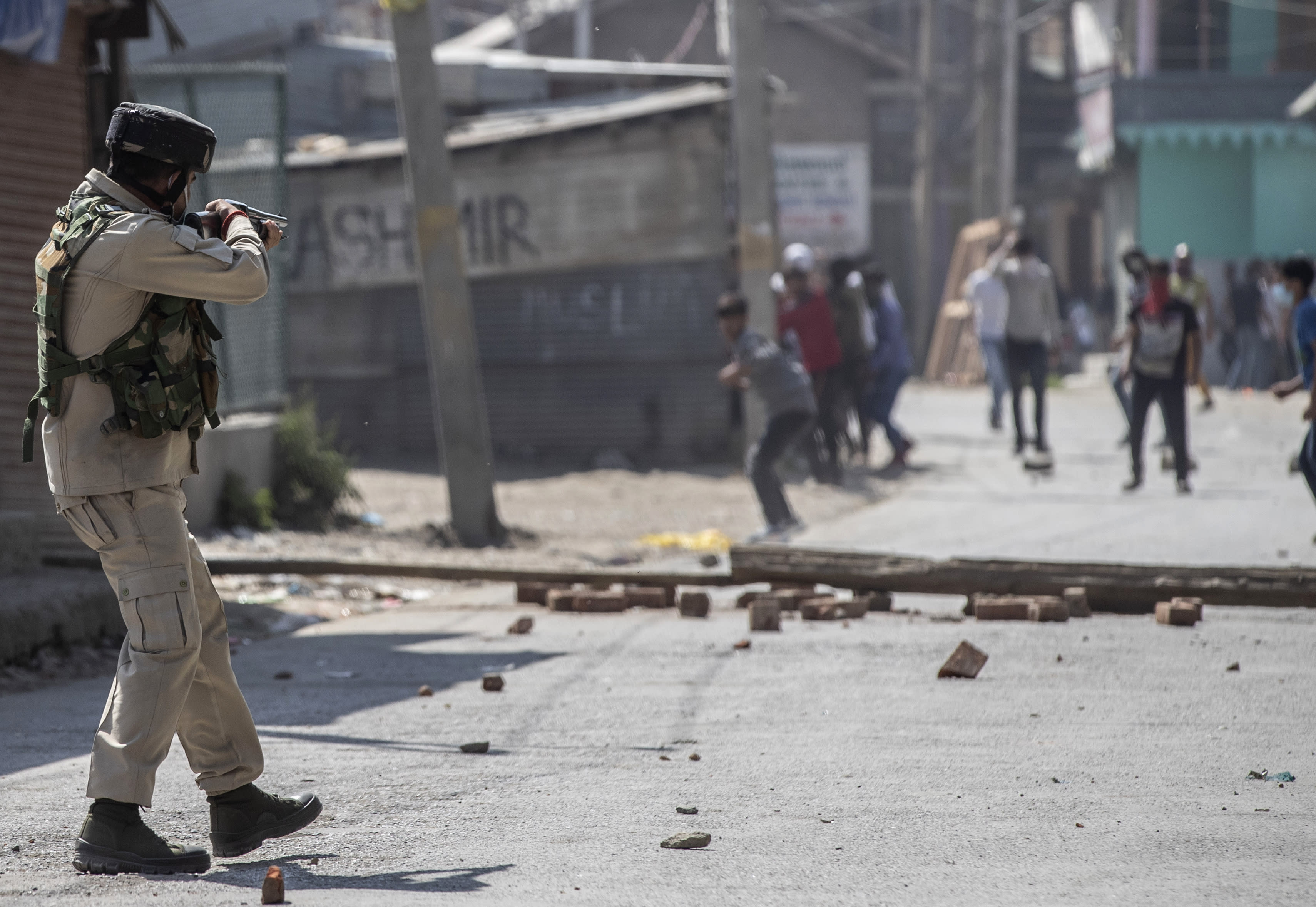 An Indian paramilitary soldier aims his pellet gun on Kashmiri protesters marching on the streets in solidarity with rebels engaged in a gunbattle with soldiers, in Srinagar, Indian controlled Kashmir, Thursday, Sept. 17, 2020. The gunfight erupted shortly after scores of counterinsurgency police and soldiers launched an operation based on a tip about the presence of militants in a Srinagar neighborhood, Pankaj Singh, an Indian paramilitary spokesman, said. (AP Photo/Mukhtar Khan)