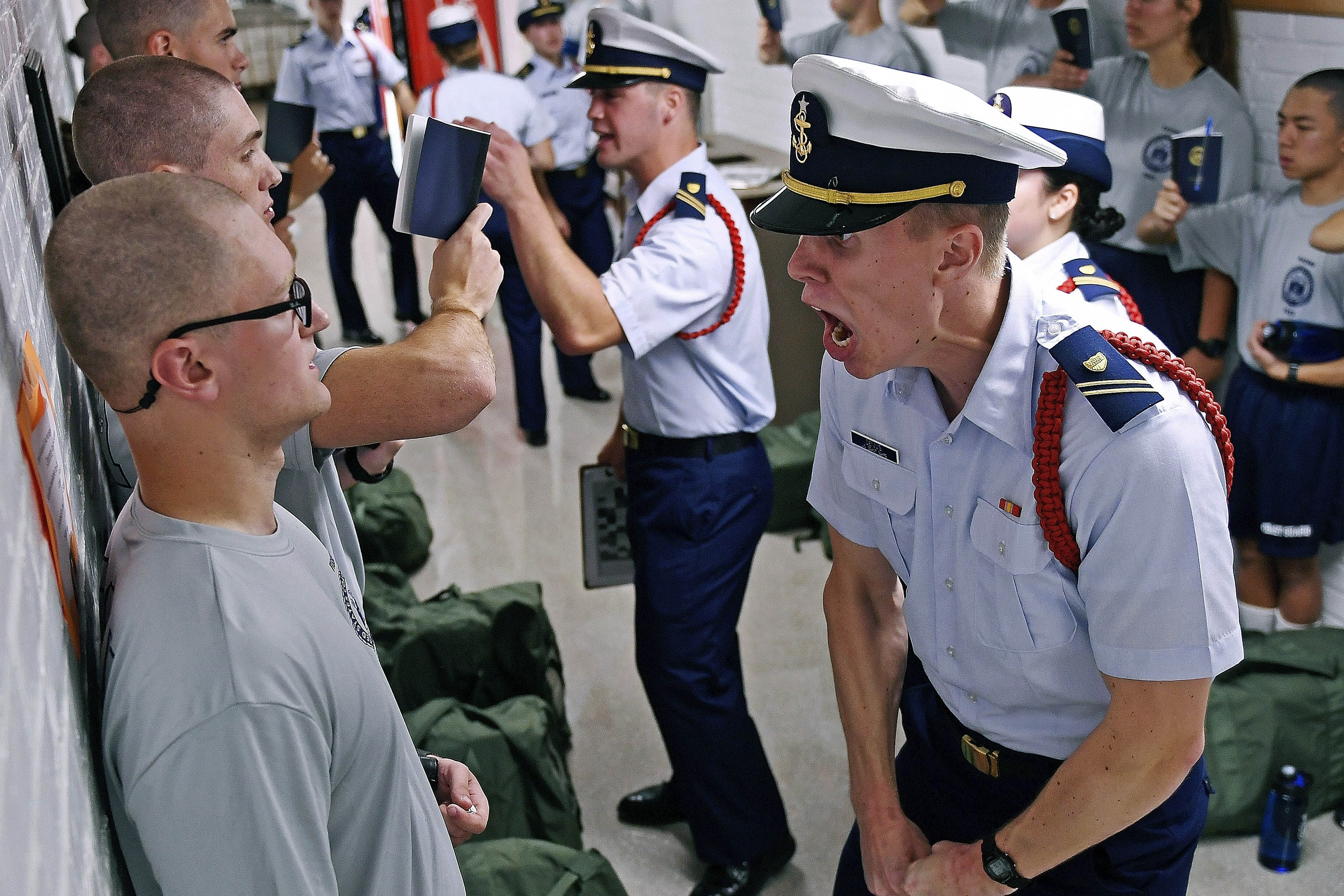"""FILE - In this July 1, 2019, file photo, Whisky 2 company Cadre Jacob Denns, right, shouts instructions to swab Nicolas Fisher, left, of Pelham, N.H., on the first day of a seven-week indoctrination to military academy life for the Class of 2023 at the U.S. Coast Guard Academy in New London, Conn. The school, like other service academies and military training centers, has made major changes because of the coronavirus pandemic. That means the eight weeks of boot camp for new cadets, known as """"Swab Summer,"""" will be much different. There will be no haircuts, no drilling, no running as a group from place to place, no lining up against the wall in the hall of the barracks for pushups. (Sean D. Elliot/The Day via AP, File)"""