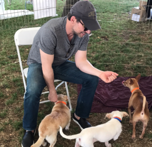 Christian Slater plays with puppies at the NKLA Super Adoption on Saturday. (Photo: Christian Slater via Instagram)