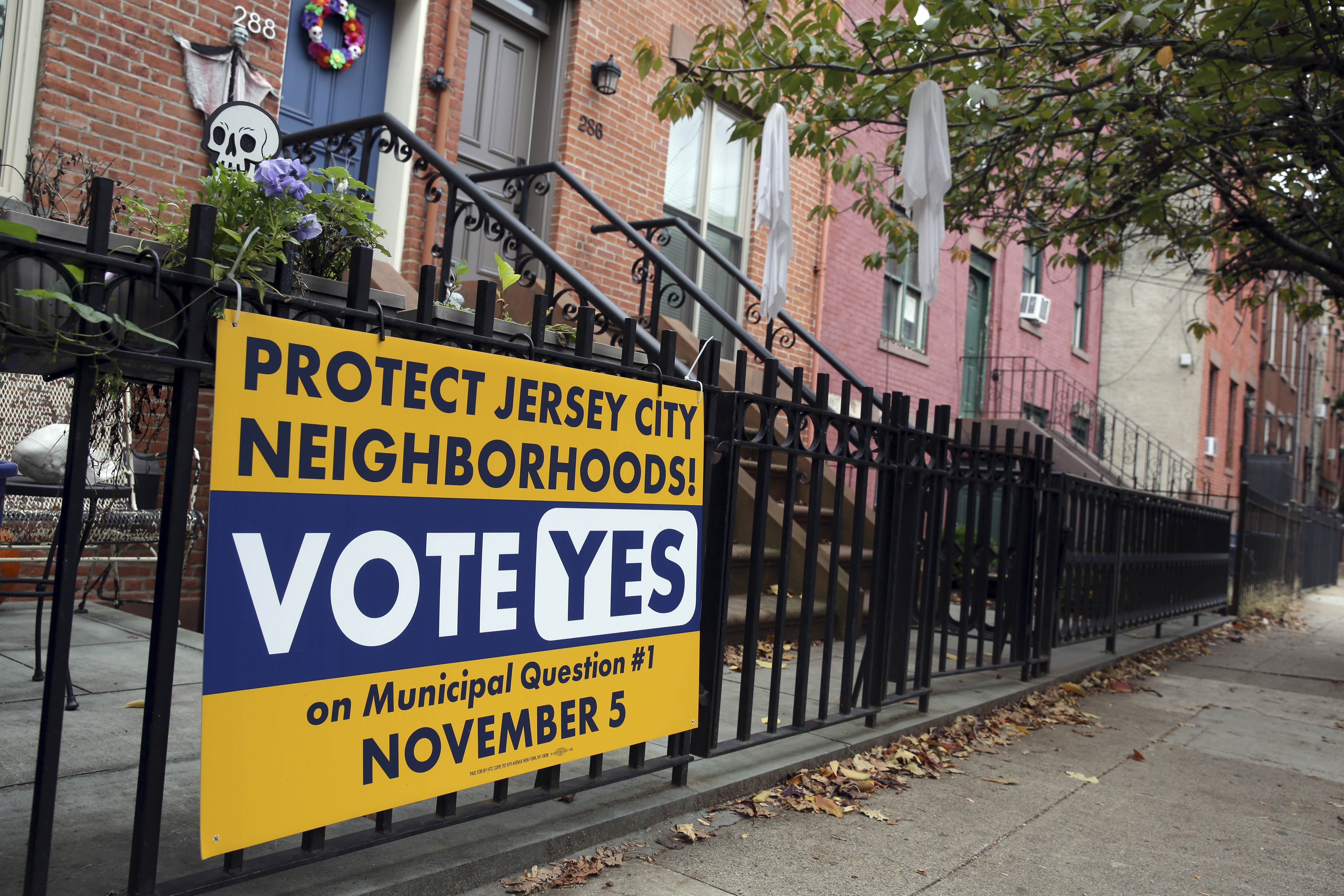 A sign urging people to vote on municipal question #1 is displayed in Jersey City, N.J., Tuesday, Nov. 5, 2019. Residents of New Jersey's second-largest city will decide Tuesday whether its increasing popularity as an affordable short-term rental option across the river from New York City has reached the point where restrictions are needed to rein in some of the unwanted byproducts.(AP Photo/Seth Wenig)