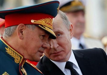 Russian President Vladimir Putin speaks with Defence Minister Sergei Shoigu as they attend the Navy Day parade in St. Petersburg