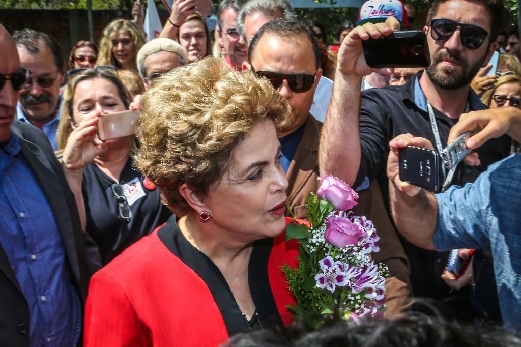 Former brazilian president Dilma Rousseff, of the leftist Workers' Party, arrives at a polling station in Porto Alegre on October 2, 2016 Brazilians furious at recession and corruption voted Sunday in municipal elections amid heightened security after a series of murders of candidates. Among the first to cast his ballot in the financial capital Sao Paulo was Brazilian president Michel Temer from the center-left PMDB party, who took over the presidency in August after turning on his former leftist ally Dilma Rousseff and helping to force her from the top job in an impeachment vote. (AFP Photo/Gustavo Roth)
