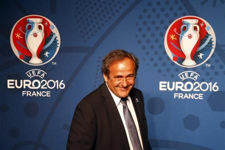 UEFA President Platini walks in front of the UEFA EURO 2016 logo at a news conference in Paris