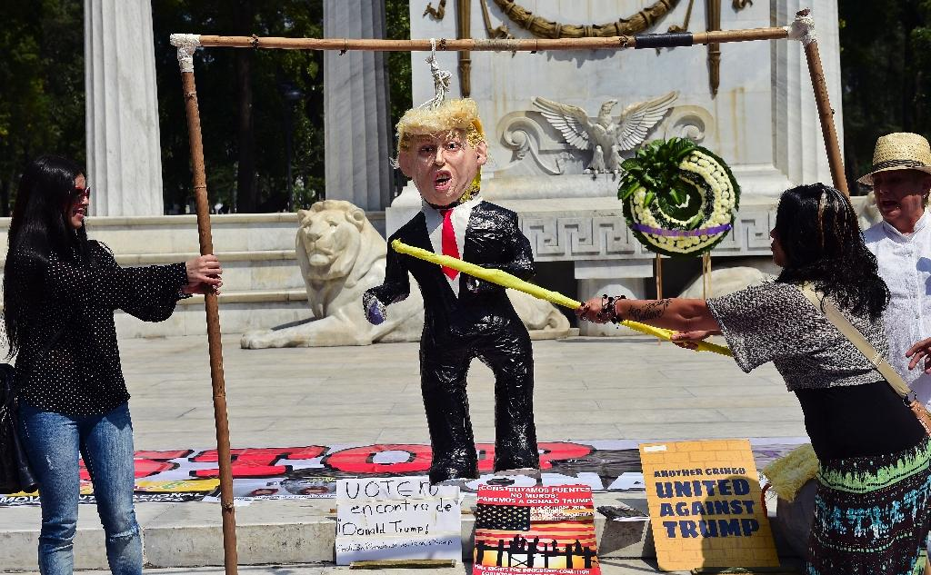 A woman hits a pinata of Donald Trump during a protest in Mexico City, on October 12, 2016 (AFP Photo/RONALDO SCHEMIDT)