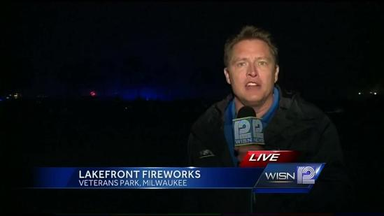 Crowds watching fireworks dealing with cold and rain