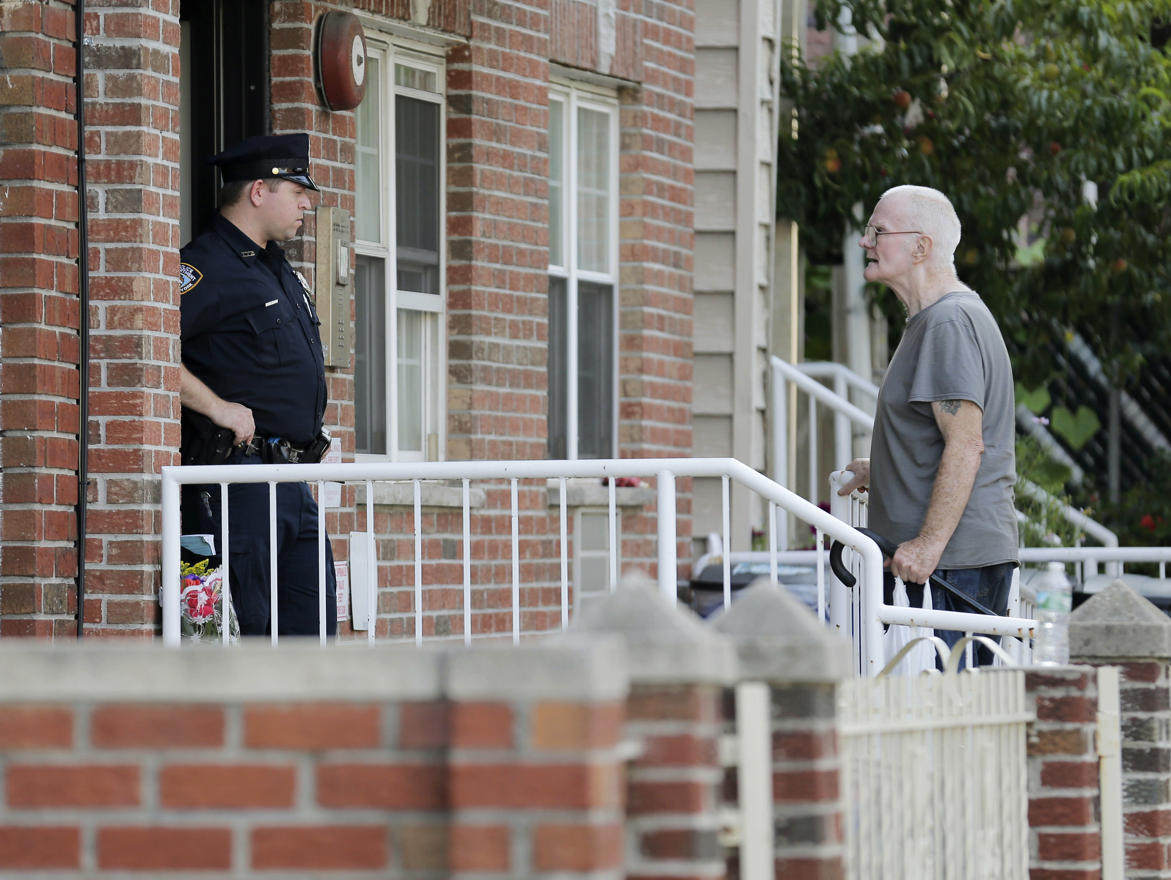 A police officer, left, talks with James Shields, Sr. in front a building where there was a shooting with multiple fatalities, including his son, in the Queens borough of New York, Tuesday, July 31, 2018. Police said the murder-suicide that left at least four people dead in New York City, may have stemmed from a trans-Atlantic custody fight. (AP Photo/Seth Wenig)