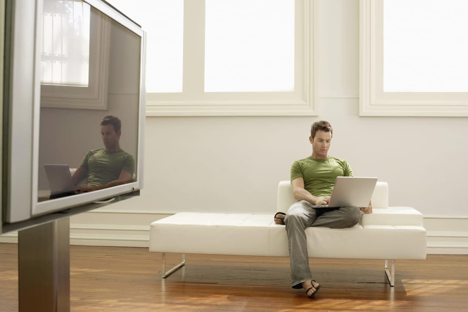Man Using Laptop on Modern Sofa