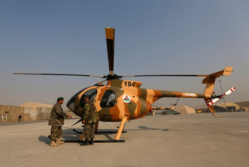 Members of the Afghan Air Force crew stand next to a helicopter at the military airport in Kabul