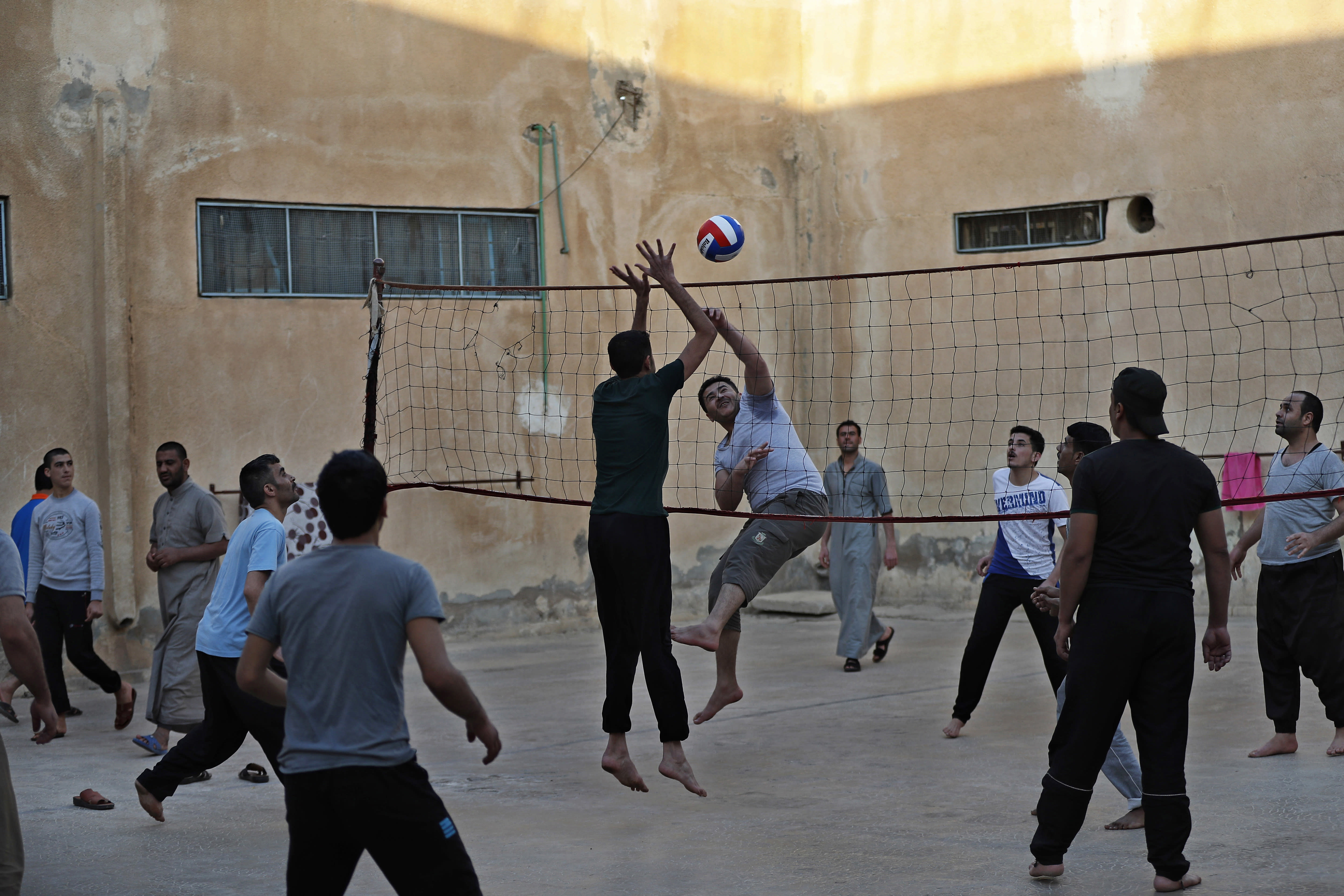CAPTION ADDITION: ADDS DETAILS ABOUT WHICH PRISON HAD RIOTS: FILE - In this April 3, 2018, file photo, prisoners play volleyball in a Kurdish-run prison housing former members of the Islamic State group, in Qamishli, northern Syria. A spokesman for Kurdish-led forces in northeastern Syria said Monday, March. 30, 2020, that they have put an end to riots by Islamic State militants in a prison there. The riots broke out late on Sunday in a prison in the town of Hassakeh and lasted several hours. Kurdish authorities run more than two dozen detention facilities scattered around northeastern Syria, holding about 10,000 IS fighters. (AP Photo/Hussein Malla, File)