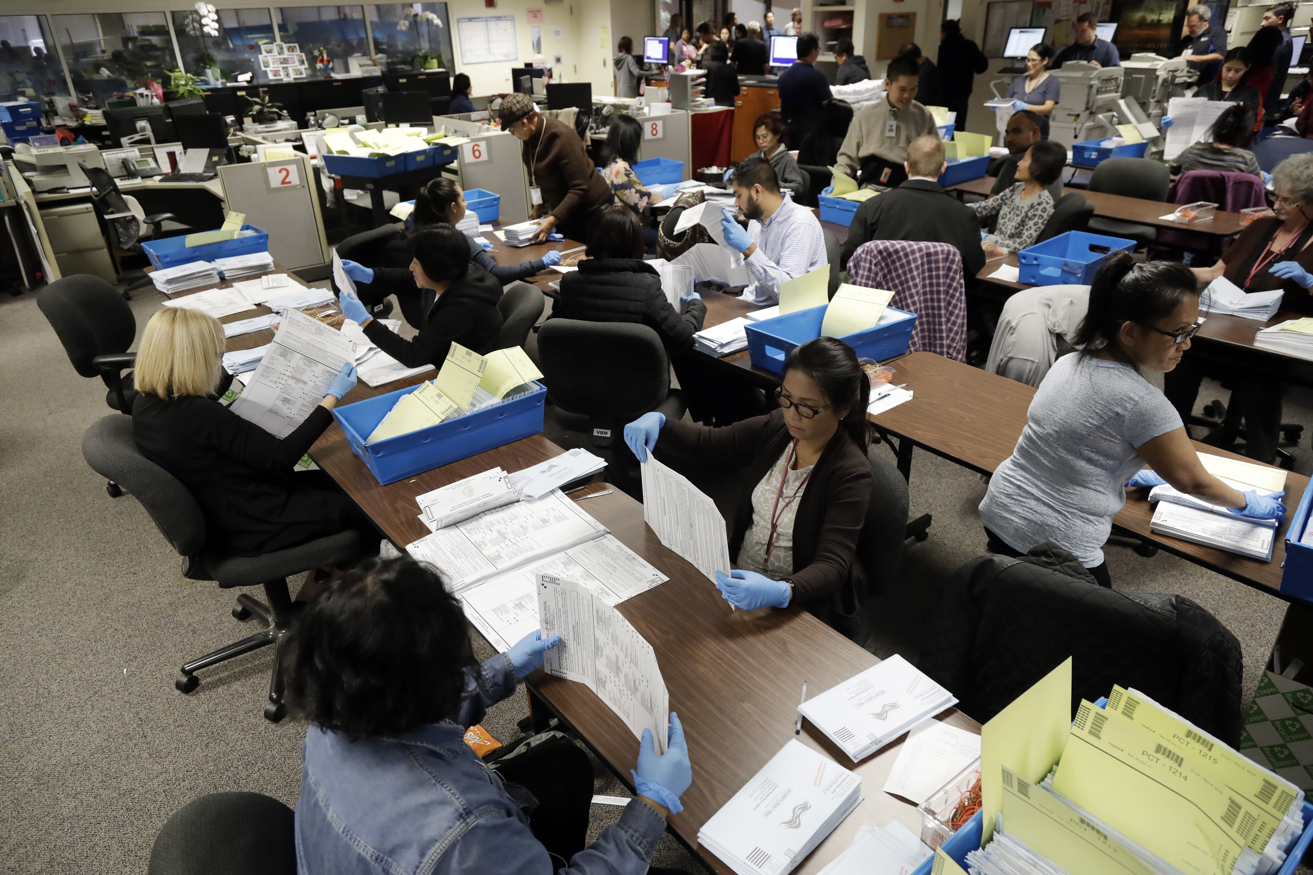 FILE - This Nov. 4, 2016, file photo shows mail-in ballots being sorted at the Santa Clara County Registrar of Voters in San Jose, Calif. Over 100,000 mail-in ballots were rejected by election officials in California's March 2020 presidential primary, highlighting a glaring gap in the effort to ensure every vote is counted as a national dispute rages over the integrity of vote-by-mail elections. (AP Photo/Marcio Jose Sanchez, File)
